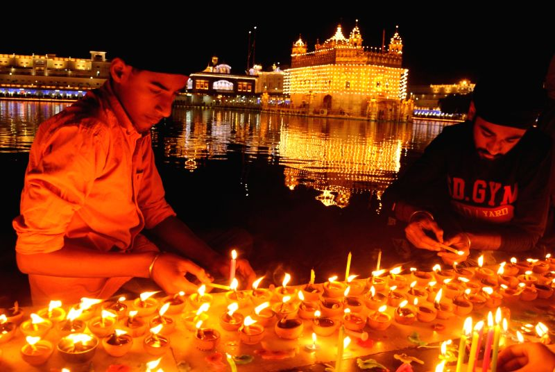 Youths light candles at the Golden Temple on Guru Nanak Jayanti, in Amritsar