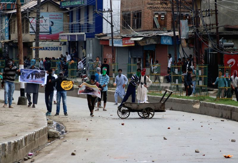 Youths pelt stones on security personnel during a demonstration in Srinagar, on May 13, 2016.