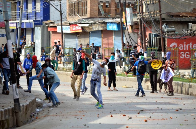 Youths pelt stones on security personnel in Srinagar on May 6, 2016.