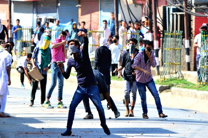 Youths pelt stones on security personnel in Srinagar on May 20, 2016.