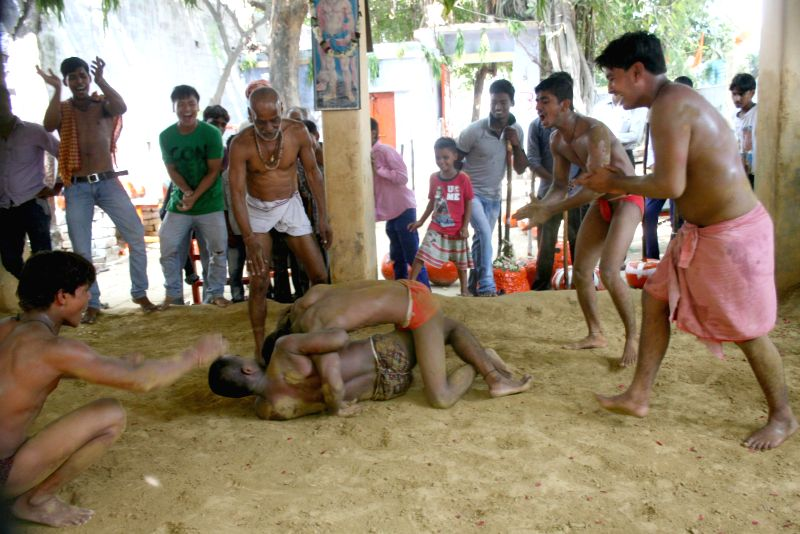 Youths practice wrestling at an akhara in Varanasi on August 1, 2014.