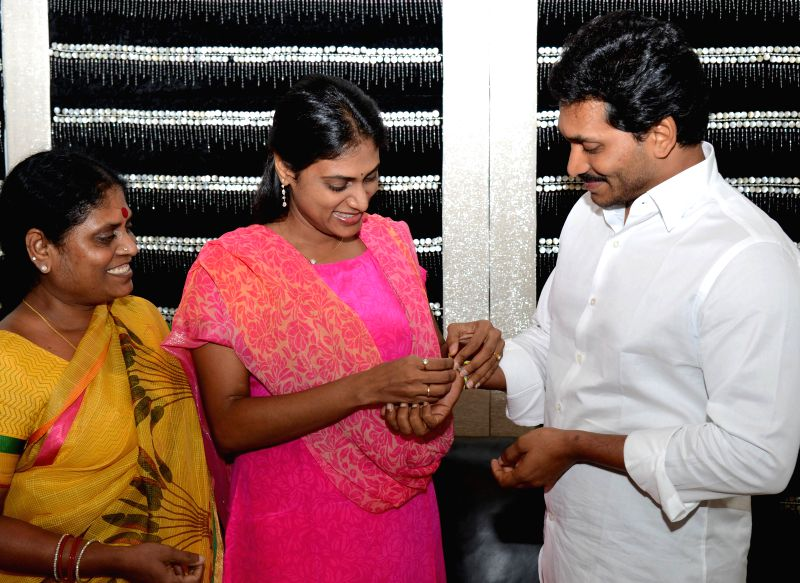YSR Congress leader and the sister of party chief YS Jaganmohan Reddy, Y. S. Sharmila ties a `rakhi` on the wrist of her brother on Raksha Bandhan in Hyderabad on Aug 10, 2014. Also seen their mother