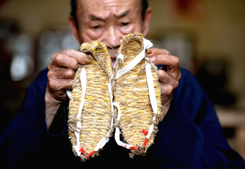 Straw sandal craftsman Chen Luoshou shows a pair of straw sandals in Buqian Village of Luoao Township in Yudu County, east China's Jiangxi Province, Aug. 1, 2014. Chen .