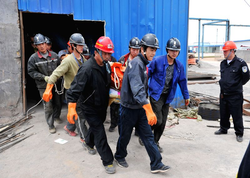 Rescuers carry the body of a victim at the Dahaize coal mine under construction by China National Coal Group Corp in Yulin City, northwest China's Shaanxi Province, ...