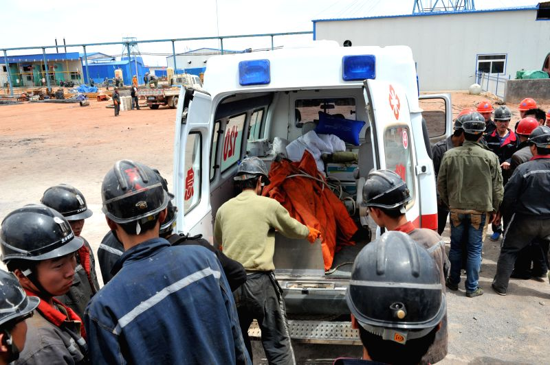 Rescuers transfer the body of a victim at the Dahaize coal mine under construction by China National Coal Group Corp in Yulin City, northwest China's Shaanxi Province,