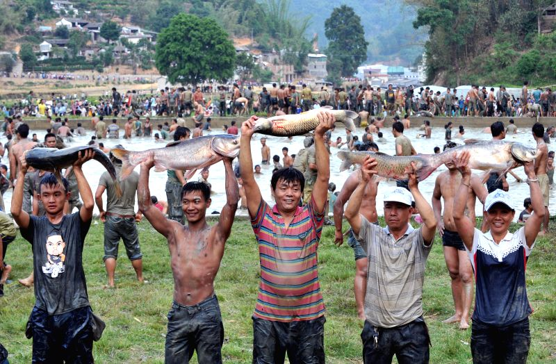 Winners of a fish-catching event present their captures during a mud games held in Luolong Village of Mojiang Hani Autonomous County, southwest China's Yunnan ...