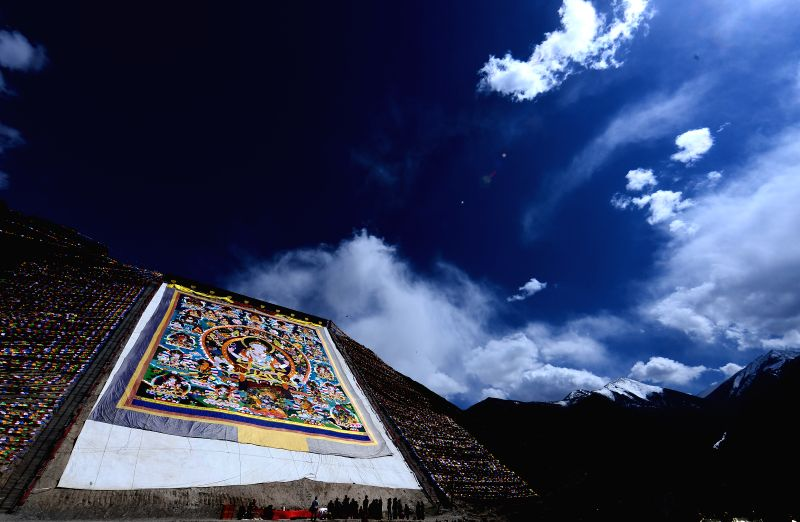 A giant Thangka embroidery bearing the names of Yushu Earthquake victims is unfurled during a Ghyo-Ku ceremony at the Dangka Monastery in Yushu, northwest China's ..