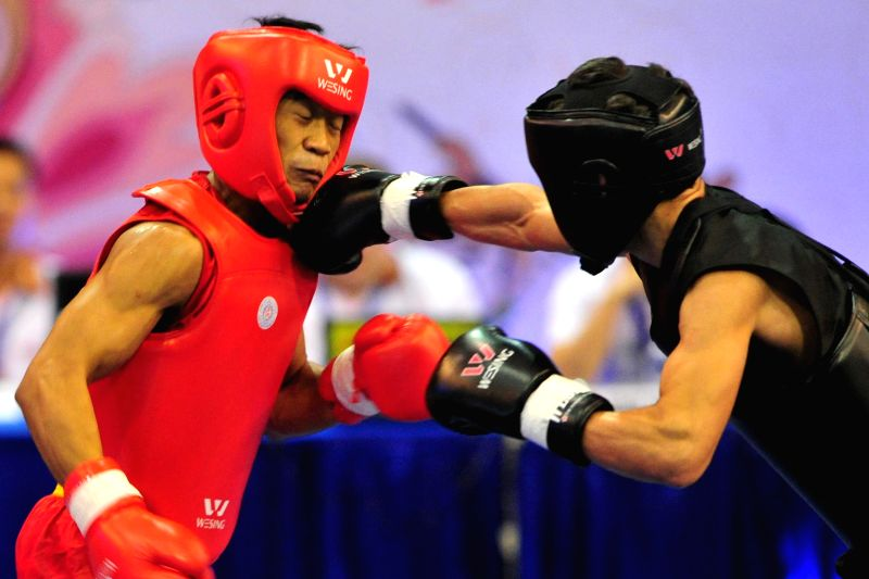Yusuf Widianto (L) of Indonesia fights against Amanbekov Avazbek of Kyrgyztan during men's 56kg Sanda semi final match at the 13th World Wushu Championships 2015 in ...