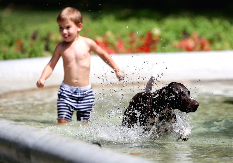 ZAGREB, Aug. 7, 2018 - A dog and a child play at a fountain at Zrinjevac Park in Zagreb, Croatia, on August 6, 2018. Croatia is currently experiencing high temperatures as a heatwave continues across ...