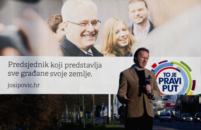 A reporter delivers a speech in front of an election campaign poster of incumbent President Ivo Josipovic in Zagreb, capital of Croatia, Dec. 26, 2014. The sixth ...