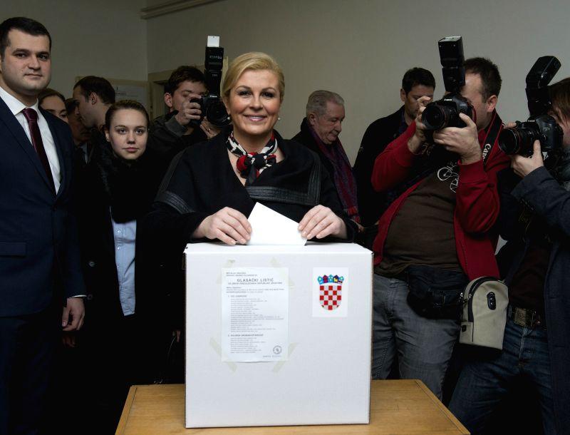Presidential candidate Kolinda Grabar-Kitarovic (C) casts her vote at a polling station in Zagreb, capital of Croatia, January 11, 2015. Croatia's presidential ...