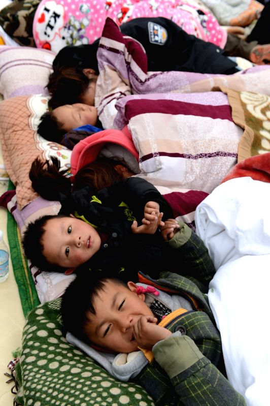 Children affected by Saturday's Nepal earthquake lie in a tent in Zham Town of Xigaze City, southwest China's Tibet Autonomous Region, April 28, 2015. Zham Town, one ...