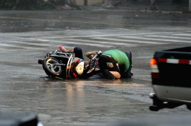 Riders fall off a motorbike due to strong wind before Super typhoon Rammasun's landfall in Zhanjiang City of south China's Guangdong Province, July 18, 2014. ...