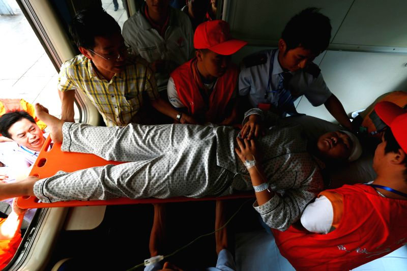 An injured man is transferred to a special train leaving for Yibin, southwest China's Sichuan Province, at the Zhaotong Railway Station in Zhaotong City, southwest .