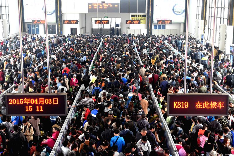 Passengers queue to take trains at Zhengzhou Railway Station in Zhengzhou, capital city of central China's Henan Province, April 3, 2015. Zhengzhou received a ...