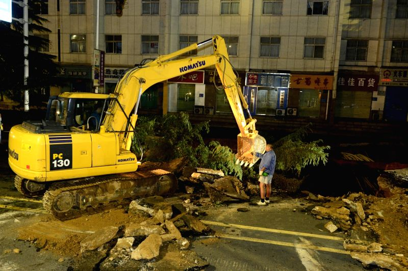 ZHENGZHOU, Aug. 2, 2016 - An excavator works at a cave-in site in Zhengzhou, capital of central China's Henan Province, Aug. 2, 2016. A road collapsed in Zhengzhou on Monday night, causing a couple ...