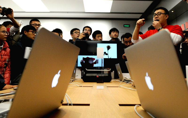 Customers try products at a newly opened Apple Store in Zhengzhou, capital of central China's Henan Province, Jan. 10, 2015. Apple inaugurated its 13th ...