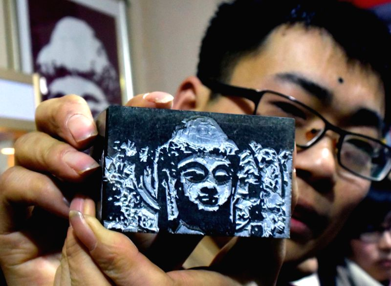 Yang Jiangtao shows a Lushena Buddha seal at an art fair in Zhengzhou, capital of central China's Henan Province, Jan. 11, 2015. Engraver Yang Jiangtao displayed .