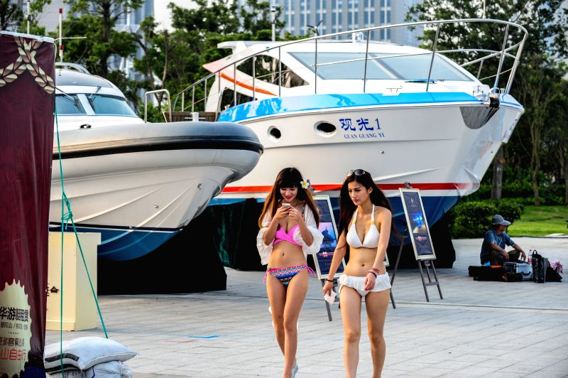 Models walk past yachts displayed during the 2014 China (Zhoushan Archepelago) International Boat Show in Zhoushan, east China's Zhejiang Province, July 11, 2014.