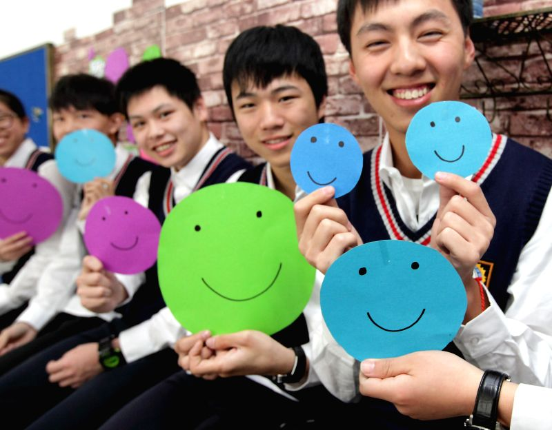 Students show their paintings of smiling faces in Zhuji City, east China's Zhejiang Province, May 7, 2014, to celebrate the upcoming World Smile Day, which falls on May