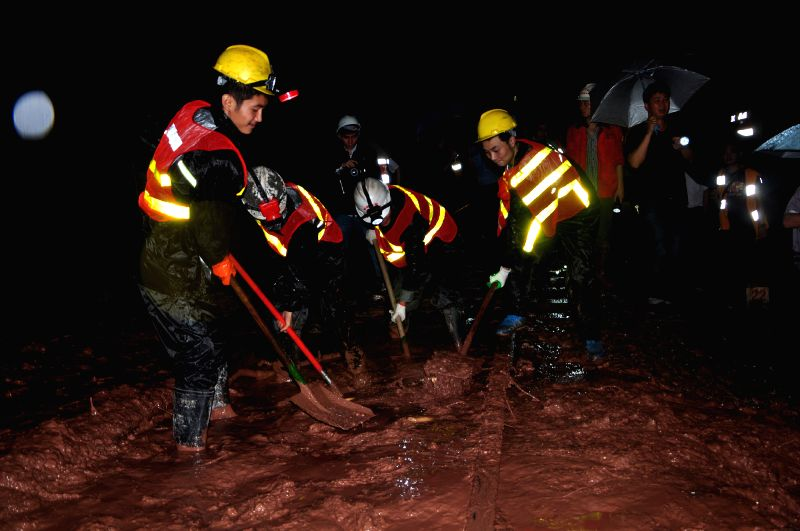 Workers clear mud off the railway in Xinzhan Township, Tongzi County, southwest China's Guizhou Province, July 15, 2014. A rain-triggered landslide on Monday affected