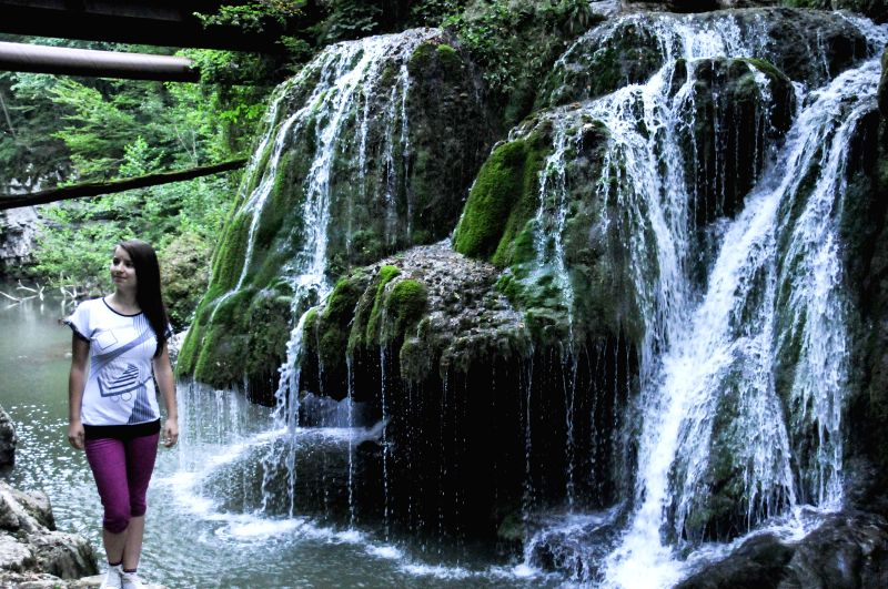A tourist poses for photos in front of the Bigar Waterfall in Caras-Severin, southwestern Romania, Aug. 26, 2014. Bigar is one of the most unusual ...