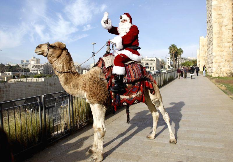 JERUSALEM, Dec. 21, 2017 - A man dressed as Santa Claus rides a camel in Jerusalem's Old City, on Dec. 21, 2017.