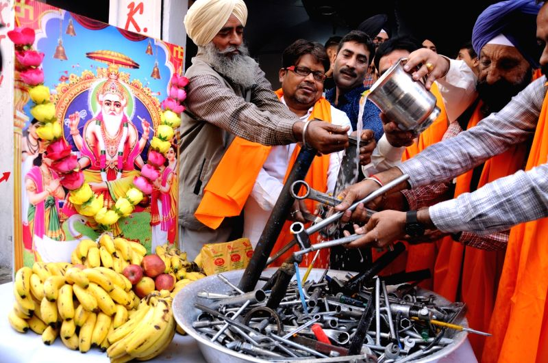 Mechanics wash their tools with milk on the occasion of Vishwakarma Puja in Amritsar, on Nov 8, 2018.