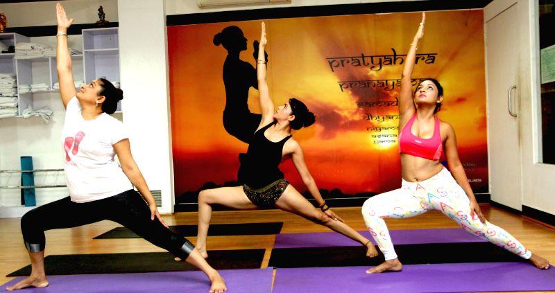 Actors Ekta Jain, Marisa Verma and yoga trainer Mandeep Kaur practice yoga ahead of International Day of Yoga in Mumbai on June 20, 2015.