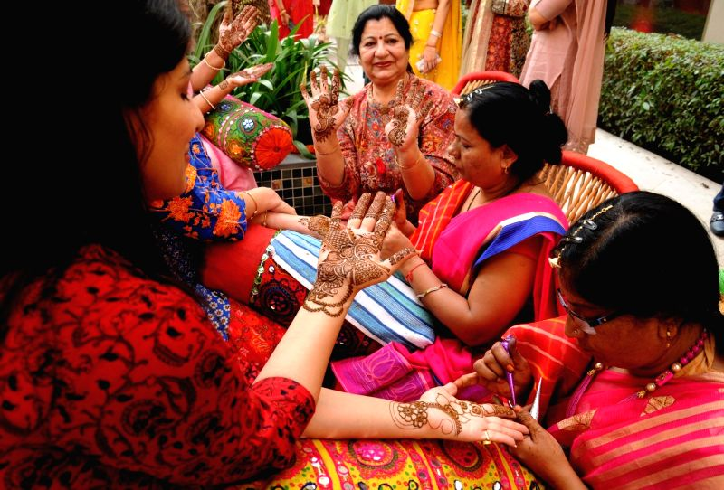 Women get Mehndi applied on their palms on the eve of Karva Chauth in Amritsar on Oct 26, 2018.