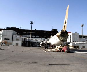Shows a severely damaged plane in Tripoli International Airport