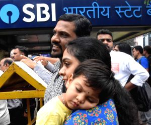 A bank employee with her child outside the State Bank of India during a two-day nationwide bank strike spearheaded by the United Forum of Bank Unions (UFBU), an umbrella body of nine ...
