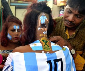 A lady gets a hair tattoo depicting the portrait of Argentine footballer Lionel Messi in Howrah on June 30, 2018.