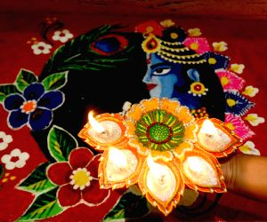 a-woman-decorates-her-rangoli-with-earthen-lamps