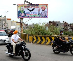 A worker arranges a billboard with a picture of Congress  Member of Legislative Assembly (MLA) Navjot Singh Sidhu in Amritsar.