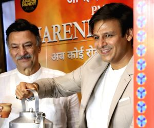 "Actor Vivek Oberoi serves tea to his father and producer Suresh Oberoi at the screening of their upcoming film ""PM Narendra Modi"" in Mumbai on May 23, 2019."