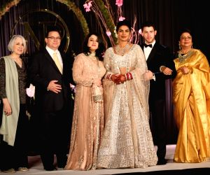 Actress Priyanka Chopra and her husband American singer Nick Jonas at their wedding reception in New Delhi on Dec 4, 2018. Also seen Nick's parents Denise Miller-Jonas and Paul Kevin ...