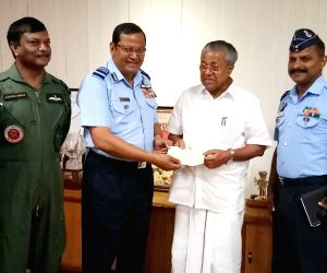 Air Officer Commanding-in-Chief, Southern Air Command, Air Marshal B. Suresh on behalf of the Chief of the Air Staff, hands over a cheque of Rs. 20 Crore to Kerala Chief Minister Pinarayi ...