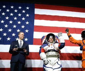 Amy Ross, a spacesuit engineer at NASA's Johnson Space Center, left, and NASA Administrator Jim Bridenstine, second from left, watch as Kristine Davis, a spacesuit engineer at NASA's Johnson Space Center, wearing a ground prototype of NASA's ne
