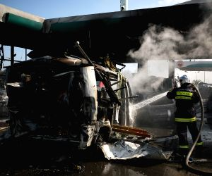 Israeli firefighters extinguish a fire that broke out after a rocket hit a gas station in Ashdod, southern Israel