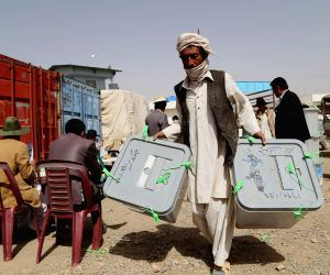 An Afghan election commission worker carries ballot boxes