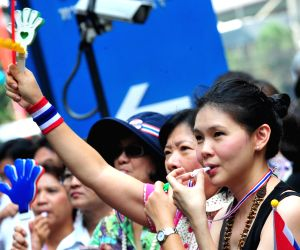 Anti-government protesters blow whistles during a rally at Asok district