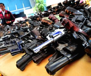 Thai policemen manage seized guns to be destroyed at Ironworks factory near Bangkok, Thailand