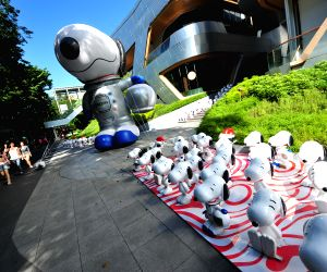 Bangkok (Thailand):  A tourist takes photos of snoopy models
