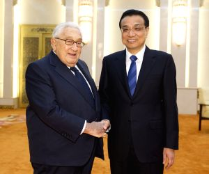 Li Keqiang shakes hands with Henry Kissinger during their meeting in Beijing