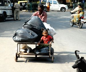 A child sits on a cart laded with scraps