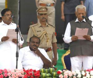 Bengaluru: Karnataka Governor Vajubhai Vala administers the oath of office to Congress leader G. Parameshwara, during a swearing-in ceremony at Vidhana Soudha in Bengaluru on May 23, 2018. ...