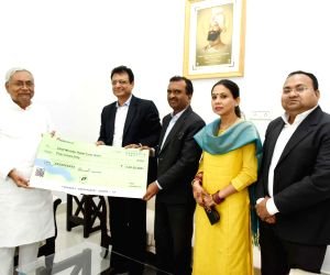 Bihar Chief Minister Nitish Kumar receives a cheque of Rs 5 Crore from the officials of ICICI Bank as a contribution towards the Chief Minister's Relief Fund, in Patna on Sep 4, 2019.