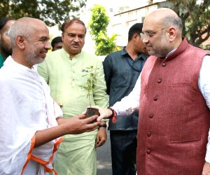 BJP chief Amit Shah receives a sapling from a local during his visit to writer Siddalingaiah's residence, in Bengaluru on April 18, 2018.