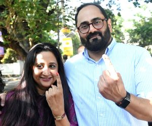 BJP Rajya Sabha MP Rajeev Chandrasekhar along with his wife Anju Chandrasekhar shows their finger marked with phosphoric ink after casting their vote at a polling booth during Karnataka ...